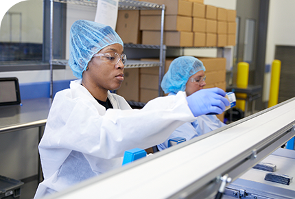 Two women working alongside a PharmFilm® manufacturing line